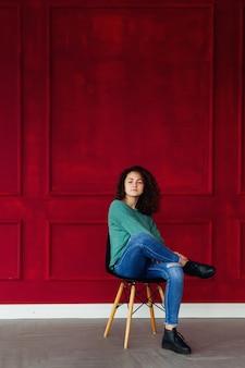 Brunette aux cheveux bouclés assis sur une chaise sur un mur rouge décoré