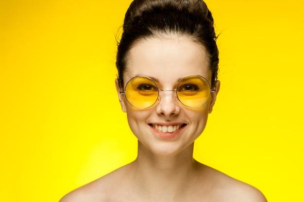 Brunette aux épaules nues lunettes jaunes look attrayant fond isolé. photo de haute qualité