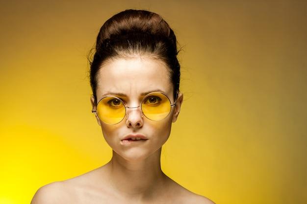 Brunette aux épaules nues lunettes jaunes look attrayant. photo de haute qualité