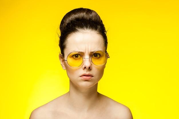 Brunette aux épaules nues portant des lunettes jaunes vue recadrée fond isolé mode émotion