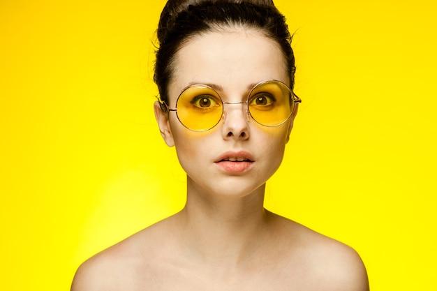 Brunette aux épaules nues portant des lunettes jaunes