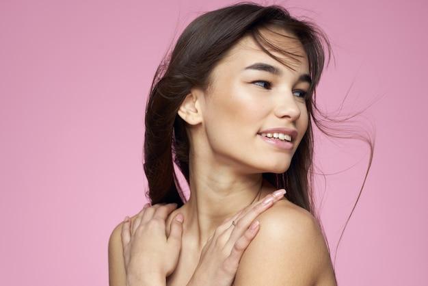 Brunette aux épaules nues tenant ses cheveux fond rose peau propre
