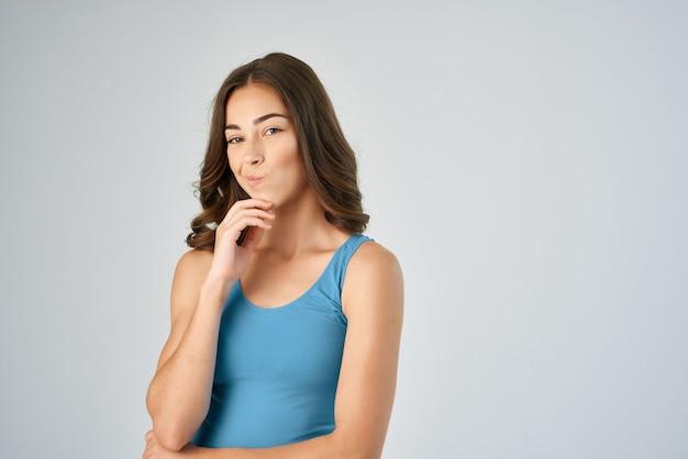 Brunette en bleu t-shirt mode mode de vie modèle de fond clair