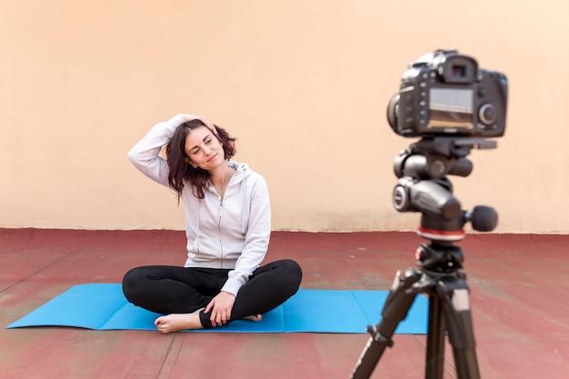 Brunette blogueuse enregistrant une routine de yoga