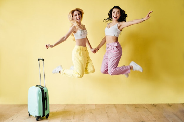 Brunette et blonde en pantalon coloré sur un mur jaune. couleur rose et jaune. voyager avec une valise à la menthe et un ananas.