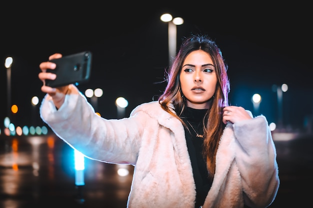 Brunette caucasienne prenant un selfie au téléphone, vêtue d'une veste en laine rose dans un parking vide. session urbaine de nuit en ville