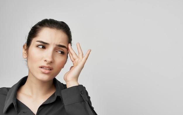 Brunette en chemise tenant face à des problèmes de santé mécontentement
