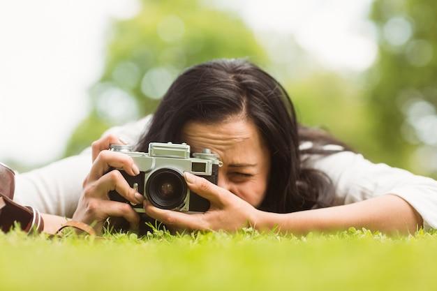 Brunette couchée sur l'herbe en prenant la photo avec l'appareil photo rétro