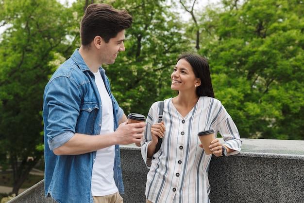 Brunette couple homme et femme avec des gobelets en papier souriant et parlant en se tenant debout dans les escaliers à l'extérieur