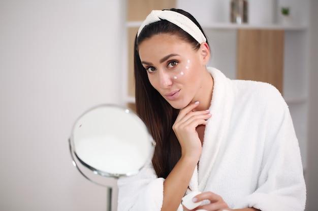 Brunette dans un peignoir appliqué de crème blanche sur le visage, soins de la peau