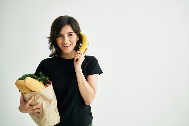 Brunette dans des sacs de t-shirts noirs avec des légumes d'épicerie