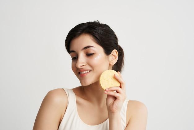 Brunette dans un t-shirt blanc avec une éponge dans ses mains cosmétiques de soins de la peau du visage