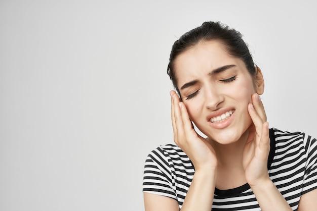 Brunette dentisterie problèmes de santé inconfort fond clair