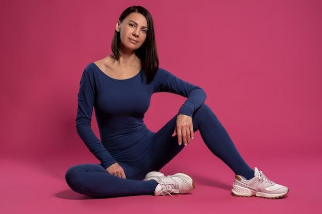 Brunette détendue en combinaison de yoga assis sur le sol