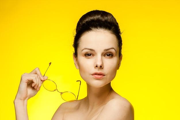 Brunette avec épaules nues lunettes de mode jaune émotions fond isolé