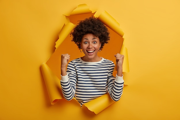 Brunette femme adulte bouclée en cavalier rayé décontracté fait un geste de victoire après avoir atteint l'objectif, se réjouit du succès, sourit largement, pose dans un trou de papier déchiré jaune