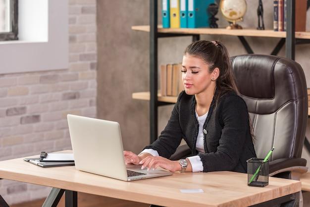 Brunette femme d'affaires à l'aide d'un ordinateur portable