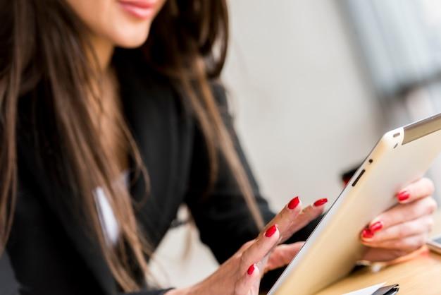 Brunette femme d'affaires à l'aide de sa tablette