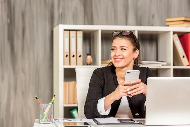 Brunette femme d'affaires à l'aide de son smartphone