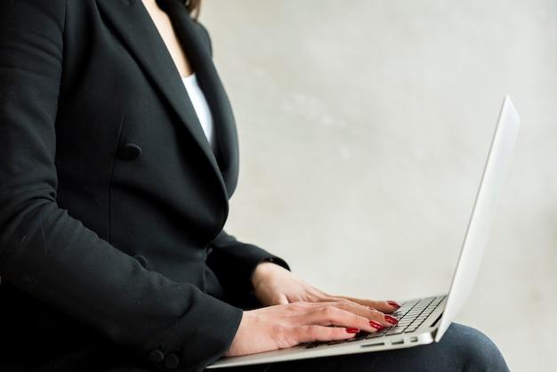 Brunette femme d'affaires chanter un ordinateur portable