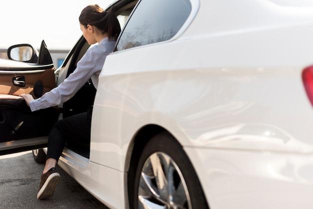 Brunette femme d'affaires avec détail de voiture