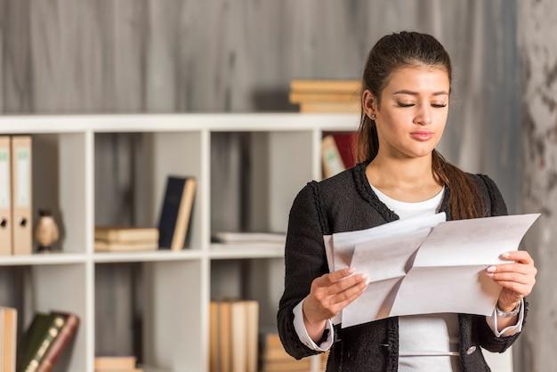 Brunette femme d'affaires lisant à son bureau