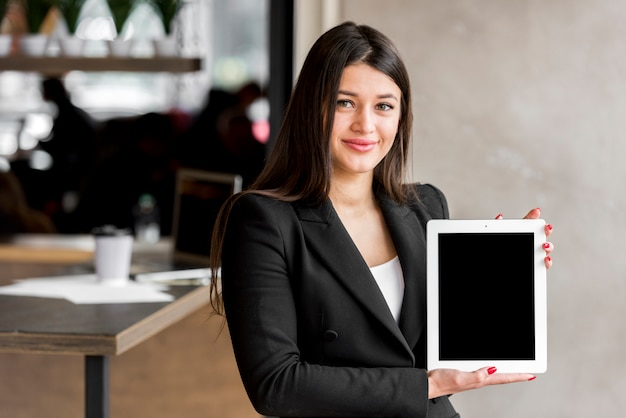 Brunette femme d'affaires montrant une tablette