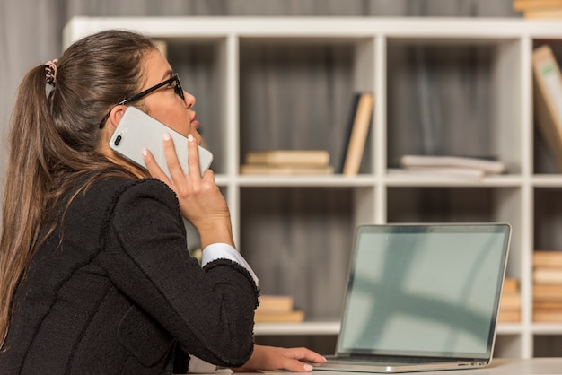 Brunette femme d'affaires parlant à son bureau