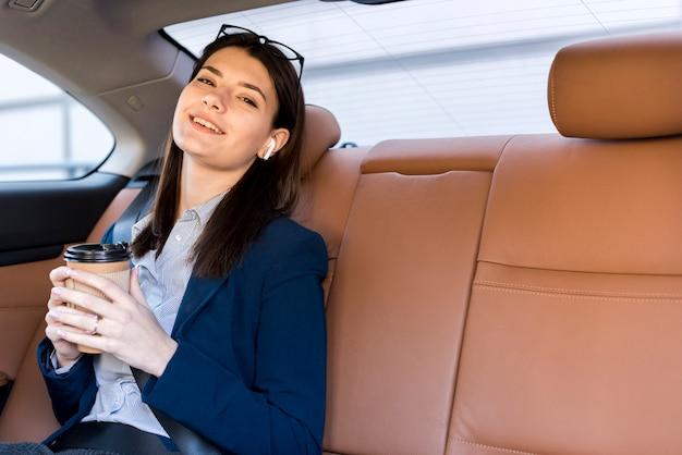 Brunette femme d'affaires posant à l'intérieur d'une voiture