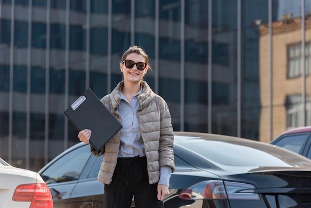 Brunette femme d'affaires posant avec des lunettes de soleil