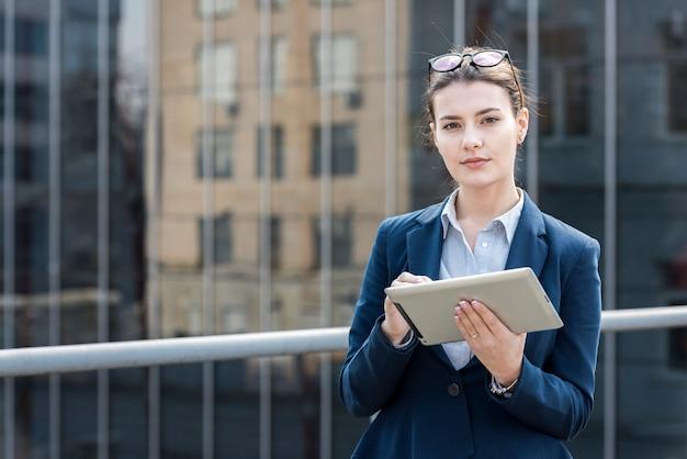 Brunette femme d'affaires posant avec une tablette
