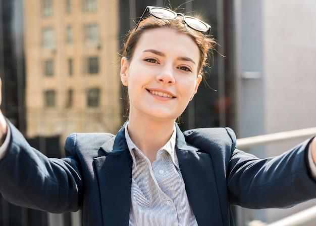 Brunette femme d'affaires prenant un selfie