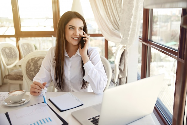 Brunette femme aux cheveux longs manager parle au téléphone portable à la réception