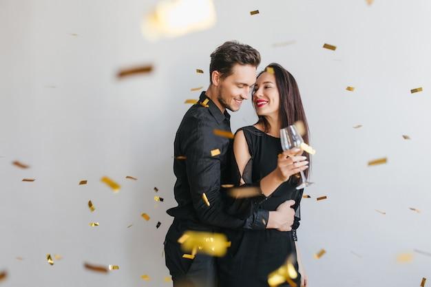 Brunette femme aux cheveux longs regarde le visage du mari avec tendresse, profitant d'une fête d'anniversaire