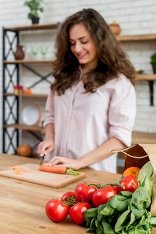 Brunette femme coupe des carottes