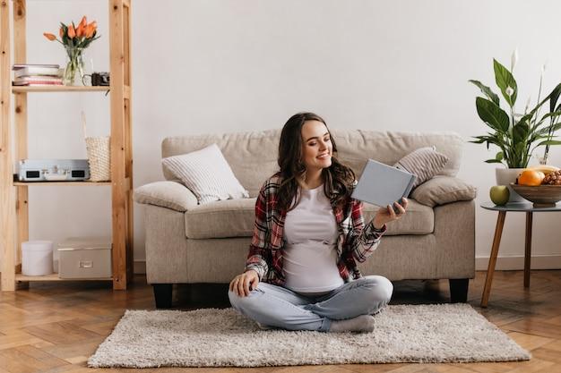 Brunette femme enceinte bouclée en chemise à carreaux rouge et chemise blanche assis sur un tapis et livre de lecture