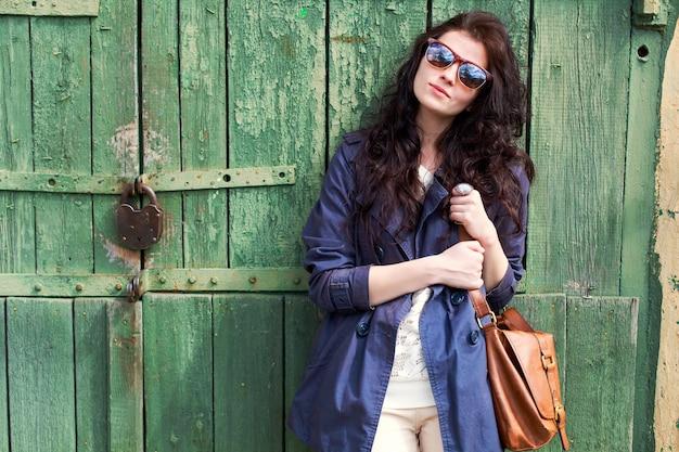 Brunette femme avec des lunettes de soleil tenant son sac à main marron