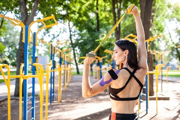 Brunette femme musclée posant avec bande de résistance de remise en forme dans le parc