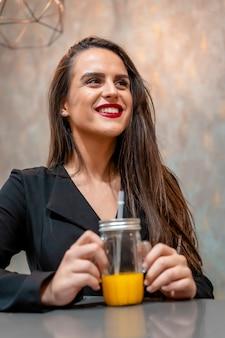 Brunette femme souriante dans un café buvant du jus d'orange