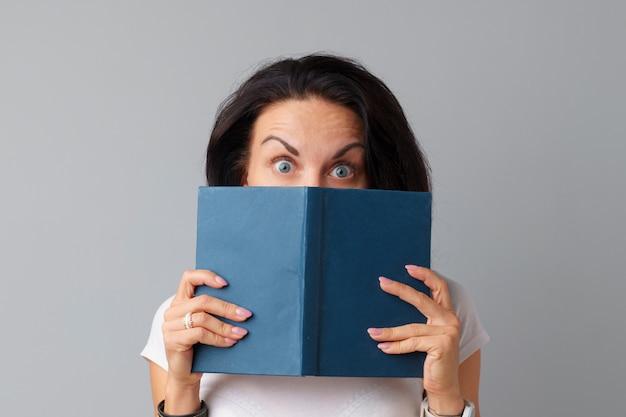 Brunette femme tenant un livre dans ses mains