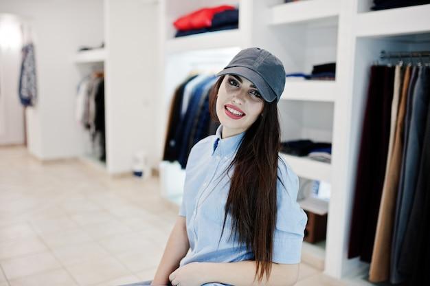 Brunette fille magnifique dans la boutique de vêtements à vêtements décontractés et casquette.