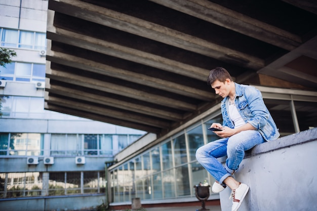 Brunette garçon en veste de jeans pose à l'extérieur
