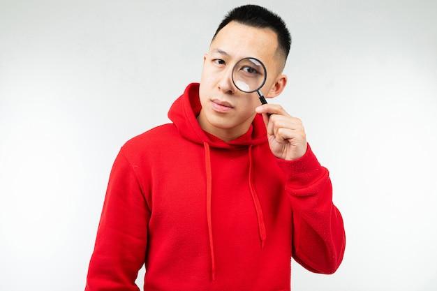 Brunette homme à capuche rouge regarde la caméra à travers une loupe sur un blanc