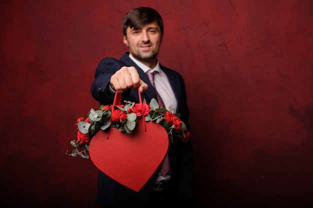 Brunette homme tenant dans une main une boîte rouge de roses