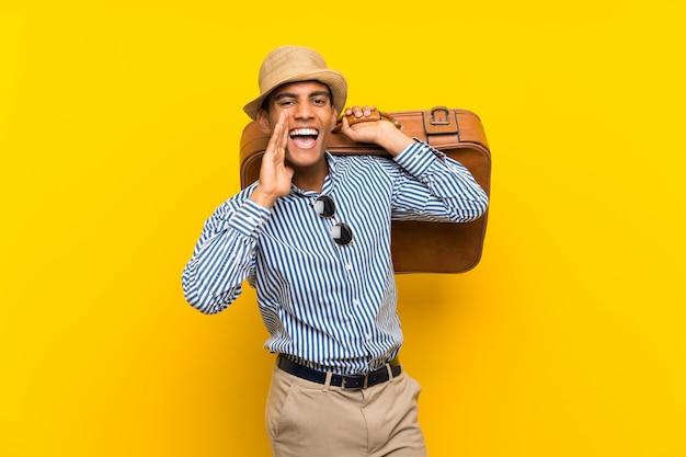 Brunette homme tenant une mallette vintage criant avec la bouche grande ouverte