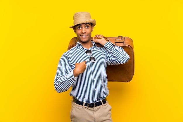 Brunette homme tenant une mallette vintage isolée jaune avec une expression faciale surprise