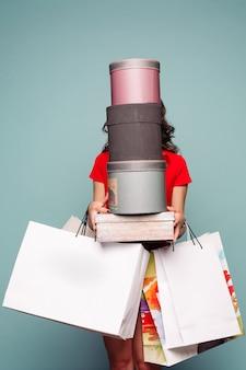Brunette incognito tenant à la main des sacs et des boîtes après le shopping.