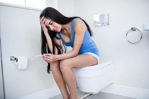 Brunette inquiète attendant le résultat du test de grossesse dans les toilettes