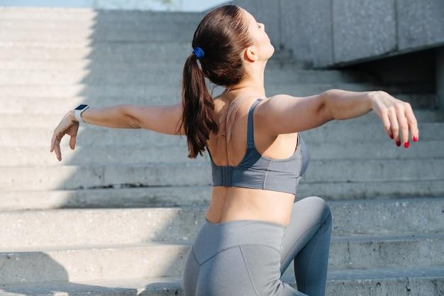 Brunette insouciante exerçant sur les longs escaliers à l'extérieur, tendant les mains
