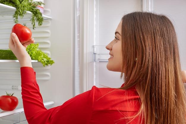 Brunette jeune femme détient des tomates mûres, se tient près d'un réfrigérateur ouvert, va faire une salade végétarienne fraîche et saine